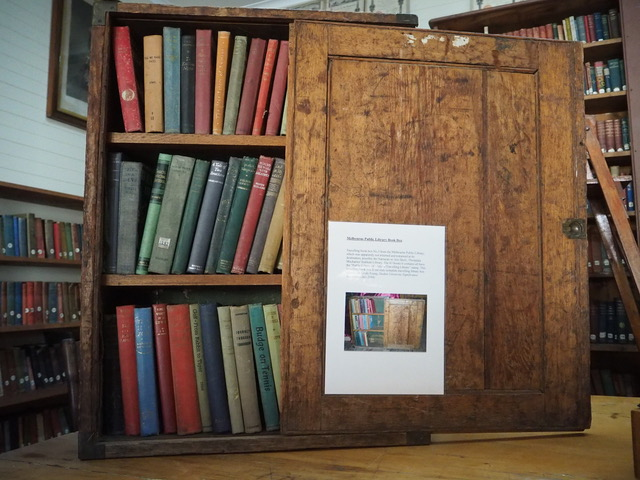 Photograph of surviving travelling library wooden box with a collection of books arranged on two shelves inside.